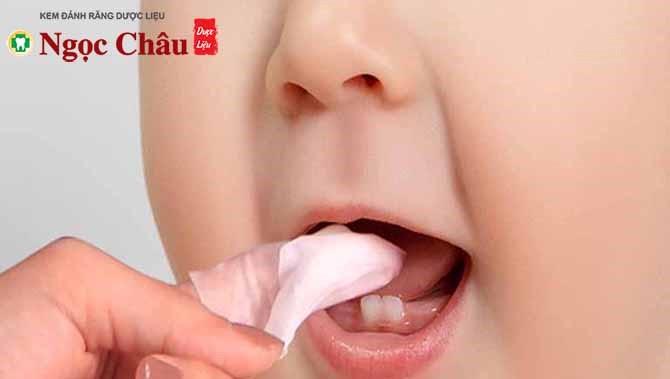 Cha mẹ có thể dùng rơ lưỡi nhúng vào nước ấm, rồi vệ sinh lưỡi và nướu cho bé